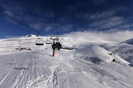 offpiste: Chair-lift and off-piste slope in sun day. Caucasus Mountains, Georgia, ski resort Gudauri. Stock Photo