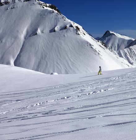 off piste: Snowboarder downhill on off piste slope with newly-fallen snow. Caucasus Mountains, Georgia, ski resort Gudauri.