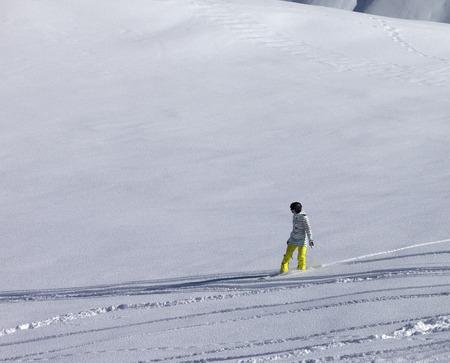 off piste: Snowboarder downhill on off piste slope with newly-fallen snow. Caucasus Mountains, Georgia. Ski resort Gudauri.