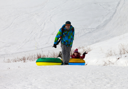 to go sledding: Father and daughter with snow tube. Caucasus Mountains, Georgia. Ski resort Gudauri.