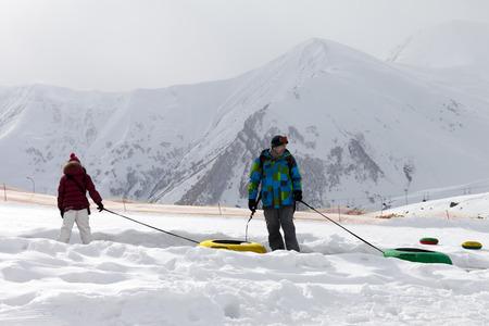 to go sledding: Father and daughter with snow tube at gray day. Caucasus Mountains, Georgia. Ski resort Gudauri. Stock Photo