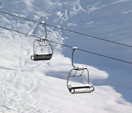 offpiste: Two chair-lift with snowdrift and off-piste slope in sun morning. Caucasus Mountains. Georgia, ski resort Gudauri.