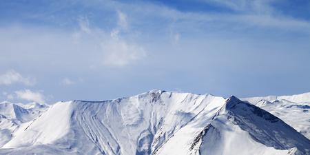 montañas nevadas: Vista panorámica sobre las montañas cubiertas de nieve con las avalanchas. Montañas del Cáucaso, Georgia, estación de esquí de Gudauri. Foto de archivo