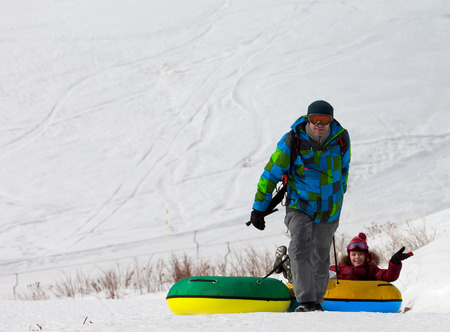 to go sledding: Father and daughter with snow tube at sun day. Caucasus Mountains, Georgia. Ski resort Gudauri. Stock Photo