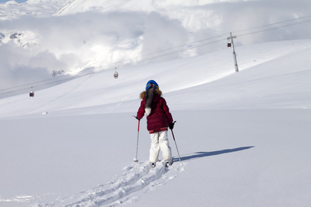 offpiste: Girl on skis in off-piste slope with new fallen snow at nice day. Caucasus Mountains, Georgia, ski resort Gudauri. Stock Photo