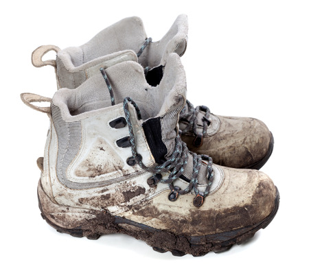 Pair of old dirty trekking boots. Isolated on white background.