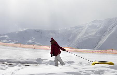 to go sledding: Girl with snow tube at sun day. Caucasus Mountains, Georgia. Ski resort Gudauri.