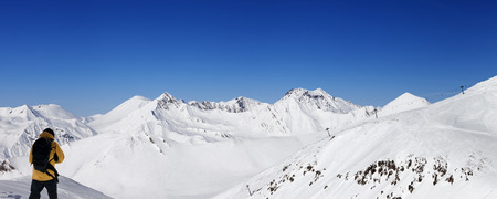 off piste: Snowboarder and panoramic view on ski resort at nice day Stock Photo
