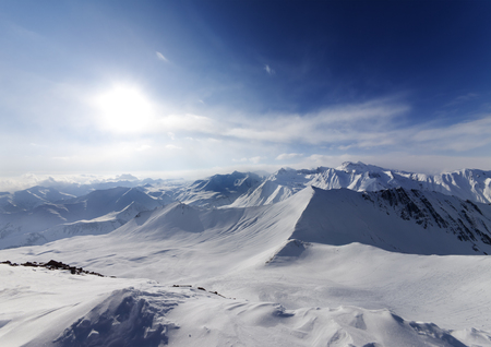 ray trace: View on off-piste slope and sky with sun. Caucasus Mountains, Georgia, ski resort Gudauri. Wide angle view.