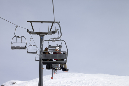 chairlift: Snowboarders on chair-lift and ski slope at gray day. Caucasus Mountains, Georgia, region Gudauri.