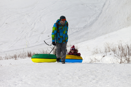 to go sledding: Father and daughter with snow tube. Caucasus Mountains, Georgia, region Gudauri.