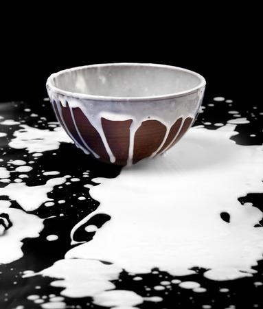 Ceramic bowl and spilled milk in black background