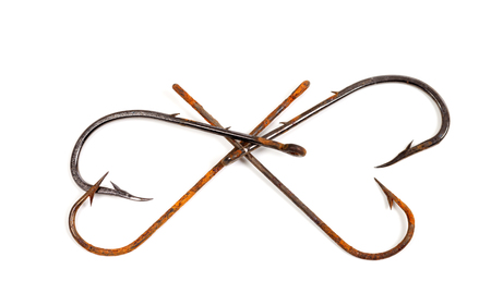 vintage design: Old rusty fish hooks in form of hearts isolated on white background