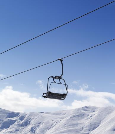 chair on the lift: Chair lift against blue sky. Caucasus Mountains, Georgia, region Gudauri. Stock Photo