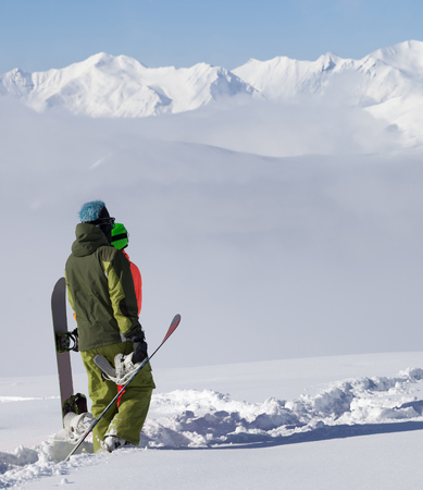 offpiste: Snowboarders on off-piste slope after snowfall. Caucasus Mountains, Georgia, region Gudauri.