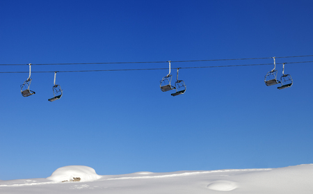 off piste: Chair-lift and blue clear sky at sun day. Greater Caucasus, Mount Shahdagh, Qusar rayon of Azerbaijan. Stock Photo