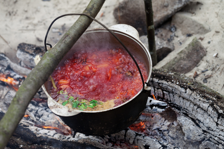 sooty: Borscht (Ukrainian traditional soup) cooking in sooty cauldron on campfire at forest
