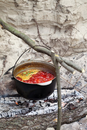 sooty: Borscht (Ukrainian traditional soup) cooking in sooty cauldron on campfire. Selective focus on pot. Stock Photo