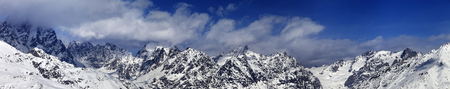 cloud capped: Large panoramic view on snowy mountains in haze at sunny day. Caucasus Mountains. Svaneti region of Georgia.