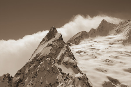 cocaine: Sepia snowy mountains. Caucasus Mountains, region Dombay. Peak Ine. Close-up. Stock Photo