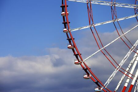 ferriswheel: Part of ferris wheel and blue sky with clouds