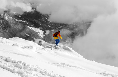 offpiste: Snowboarder on off-piste slope and mountains in fog. Caucasus Mountains, Georgia, region Gudauri. Selective color.
