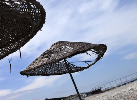 aslant: Old sunshade with hole on deserted beach in sunny day