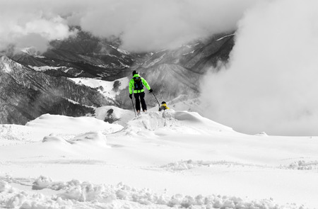 offpiste: Freeriders on off-piste slope and mountains in mist. Caucasus Mountains, Georgia, region Gudauri. Selective color. Stock Photo