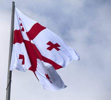 windy day: Flag of Georgia and cloudy sky at gray windy day