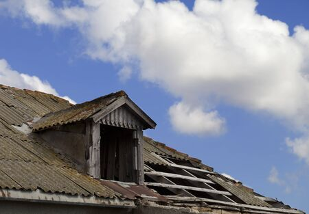 kaput: Old tile roof with holes and blue sky with clouds in sun day Stock Photo