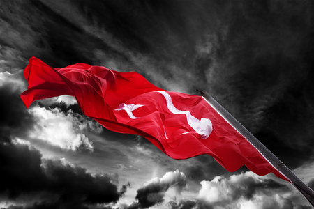 Flag of Turkey waving against black and white dark storm sky