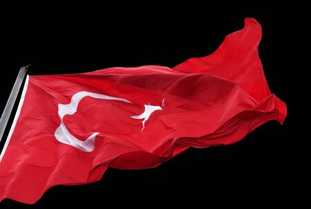 Turkish flag waving in wind. Isolated on black background.