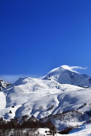 sun track: Mount Tetnuldi and off-piste slope with track from ski and snowboard in sun day. Caucasus Mountains, Svaneti region of Georgia. Stock Photo