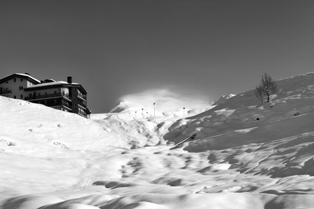 piste: Black and white view on off-piste slope and hotel in winter mountains. Caucasus Mountains, Georgia, region Gudauri.