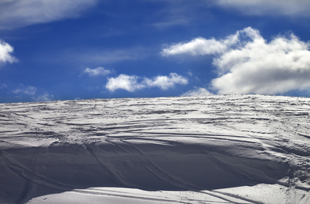 cornice: Off-piste slope and snow cornice with track from ski and snowboard in sun day Stock Photo