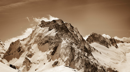 Panoramic view on snow winter mountains. Caucasus Mountains, region Dombay, mount Dombay-Ulgen. Sepia toned landscape.