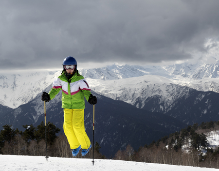 skier jumping: Young skier jumping with ski poles in sun mountains and cloudy gray sky. Caucasus Mountains. Hatsvali, Svaneti region of Georgia. Stock Photo