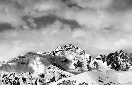 ski traces: Black and white snow slope and winter sunlight mountains in clouds. Caucasus Mountains, Svaneti region of Georgia. Stock Photo