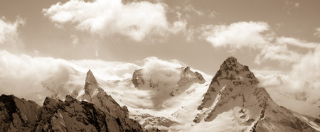 cusp: Panorama of winter mountains in cloud. Caucasus Mountains, region Dombay. Sepia toned landscape. Stock Photo