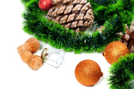 uncork: Green Christmas tinsel, Christmas-tree balls, pine cones and champagne wine cork with muselet. Isolated on white background. Selective focus.
