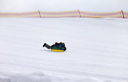 to go sledding: Snow tubing in ski resort at gray day