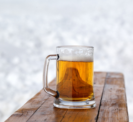 Glass mug with fresh cold beer on wooden bench in outdoor cafe at ski resort. Close-up view.