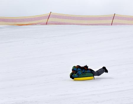 to go sledding: Snow tubing at ski resort in gray day Stock Photo