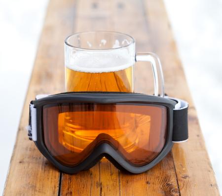 スキーゴーグル ・ スキー リゾートの屋外カフェで木製のベンチに新鮮な冷たいビールを持つガラス マグカップ