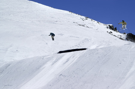 skier jumping: Snowboarder and skier jumping in snow park at ski resort on sunny winter day. Caucasus Mountains, region Dombay. Stock Photo
