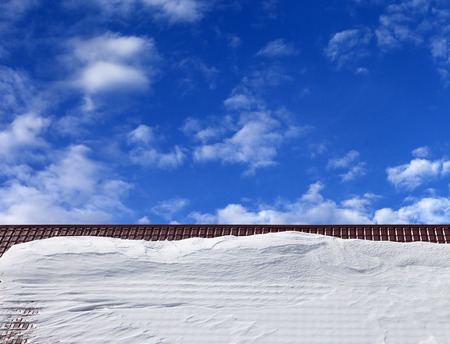 Roof in snow and blue sky with clouds in sun winter day Stock Photo