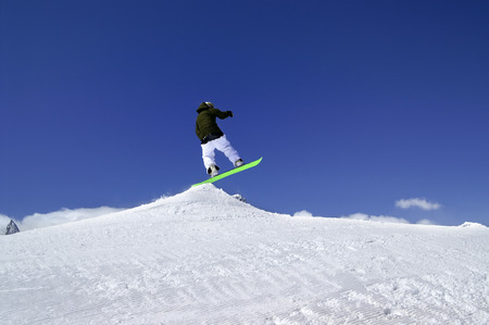 ski traces: Snowboarder jump in snow park at ski resort on sun winter day. Caucasus Mountains, region Dombay.