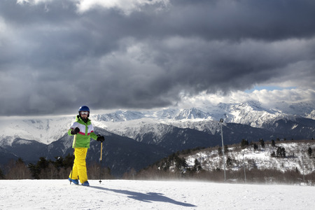 Young skier with ski poles in sun mountains and cloudy gray sky before blizzard. Caucasus Mountains. Hatsvali, Svaneti region of Georgia.