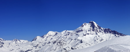 Panoramic view on off-piste slope and mount Kazbek at sun winter day. Caucasus Mountains, Georgia, region Gudauri.