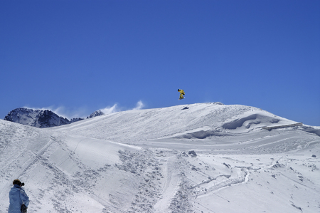 Snowboarder jumping in snow park at ski resort on sun winter day. Caucasus Mountains, region Dombay.